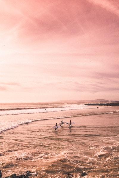 surfers ocean pink skies